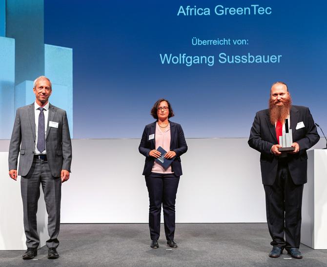 Er elektrifiziert entlegene Dörfer in Afrika Subsahara und sorgt so für Klimaschutz und Arbeitsplätze: Torsten Schreiber (rechts). Für sein persönliches Engagement gratulierten ihm Wolfgang Sussbauer von PGIM und Redakteurin Daniela Englert zum Vordenker-Award.